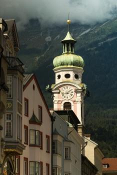 Die Spitalskirche im Sonnen schein, vor den Wolken verhangenen Alpen.